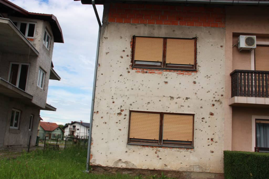 Houses in Turanj still show holes from the shelling during the Croatian War for Independence in the 1990s