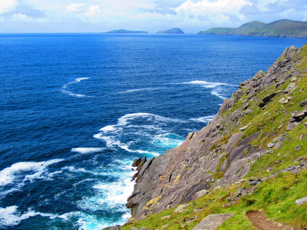 The azure water & green craggy coastline of Ireland's Dingle Peninsula...consider Dingle over the Ring of Kerry, particularly during peak tourist season. It's a must on any Irish roadtrip itinerary, you won't regret it! Tips for the drive, where to stop, and what to see!
