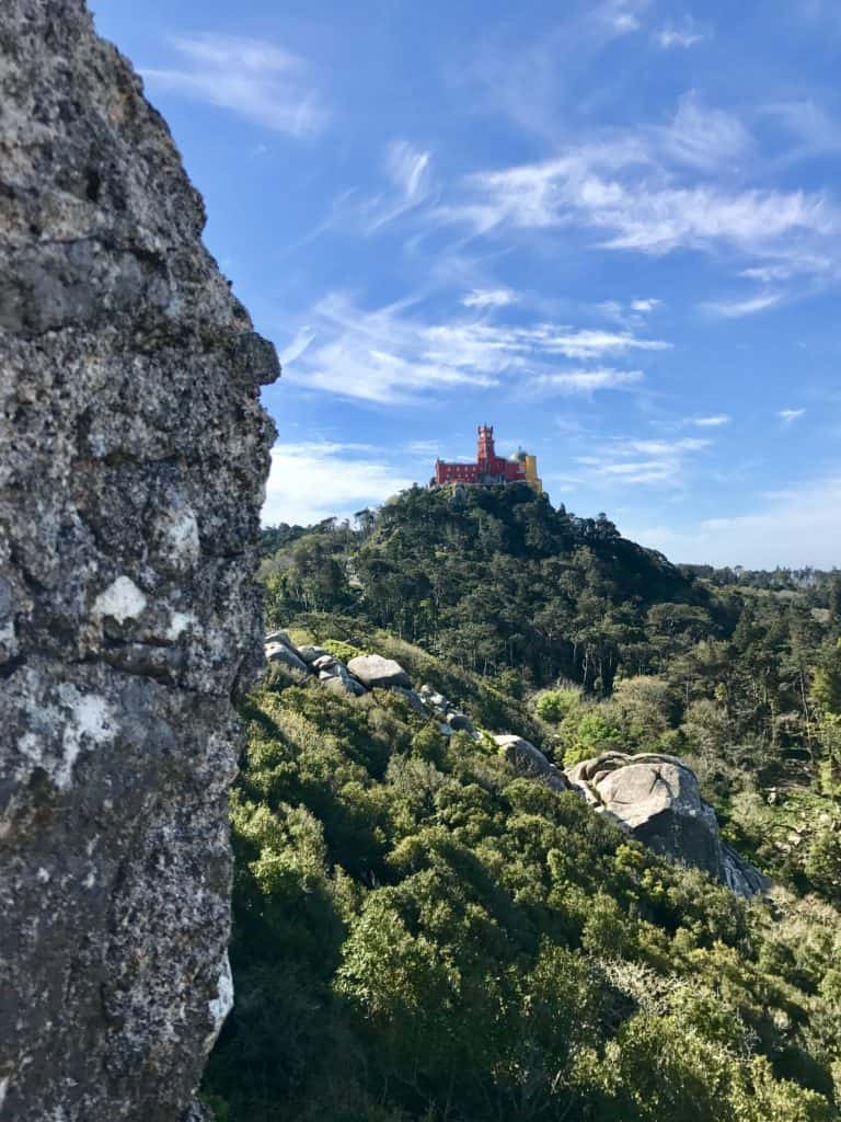 A view of gorgeous Pena Palace from the Moorish Castle | A guide to visiting magical Sintra, Portugal, a perfect guide for any first-timer | What to do in Sintra, which castles to visit, how to plan your trip | Sintra is the perfect day trip from Lisbon, but you could easily spend a few days exploring all the amazing history! #sintra #portugal